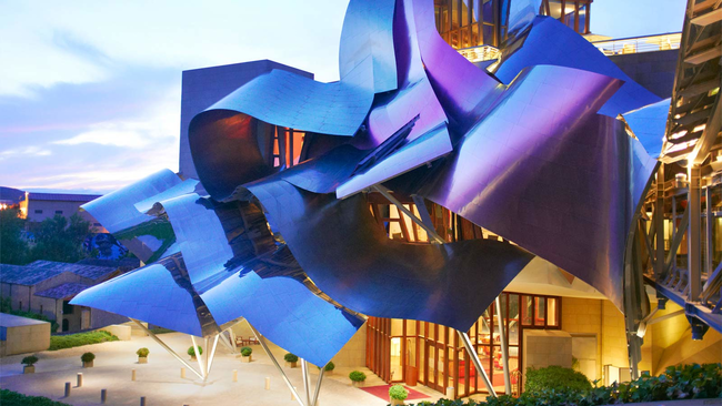 This hotel's colorful, fabric-like design was created by architect Frank Gehry. It was made from silver, gold, and pink titanium. The building's unconventional style makes it a work of art itself. It's located in the north of Spain, in the Basque country.