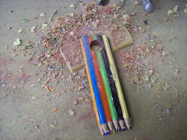 Next, he drilled a hole in the glued pencils, making the ring.
